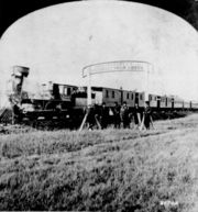 Directors of the Union Pacific Railroad gather on the 100th meridian, which later became Cozad, Nebraska, approximately 250 miles (400km) west of Omaha, Nebraska Territory, in October 1866. The train in the background awaits the party of Eastern capitalists, newspapermen, and other prominent figures invited by the railroad executives.